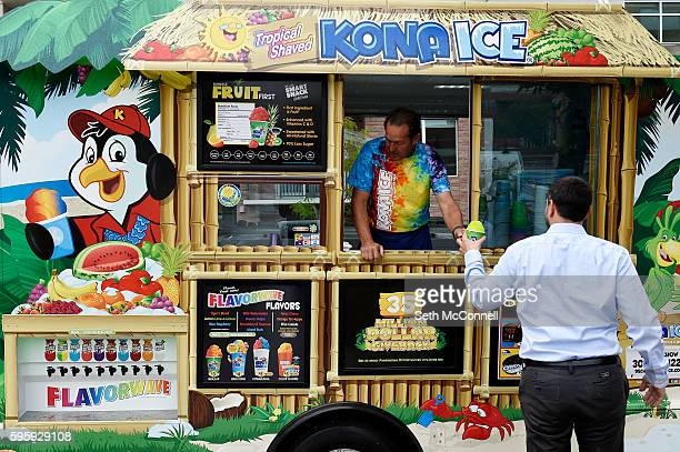 David Schow hands off a shaved ice to a customer at the Kona Shaved Ice truck in Denver Colorado on August 24 2016 Kona serves shaved ice and ice...