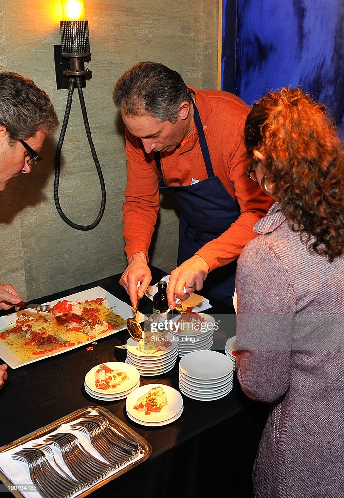 David Shalleck (C) serves food to the crowd at the Syracuse University's San Francisco Donor Reception at Waterbar Restaurant on February 5, 2013 in San Francisco, California.