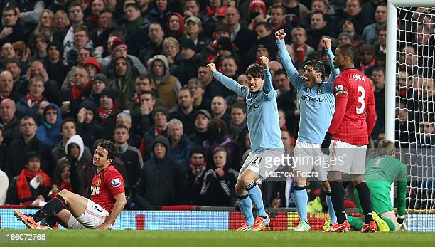 David Silva and Carlos Tevez of Manchester City celebrates James Milner scoring their first goal during the Barclays Premier League match between...