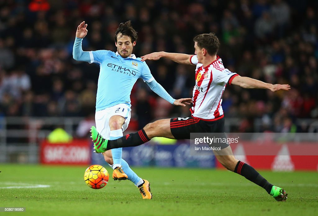 David Silva of Manchester City and Billy Jones of Sunderland compete for the ball during the Barclays Premier League match between Sunderland and Manchester City at the Stadium of Light on February 2, 2016 in Sunderland, England.