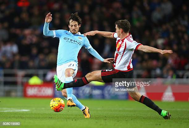 David Silva of Manchester City and Billy Jones of Sunderland compete for the ball during the Barclays Premier League match between Sunderland and...