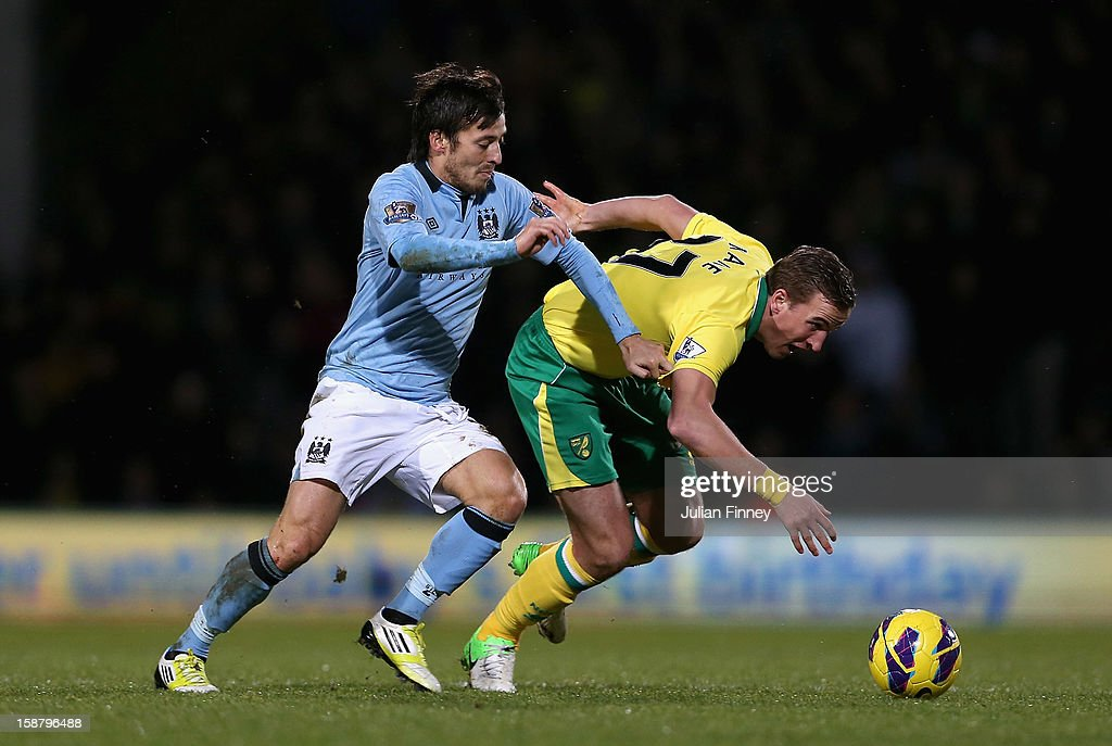 David Silva of Manchester City and Harry Kane of Norwich City tussle for the ball during the Barclays Premier League match between Norwich City and Manchester City at Carrow Road on December 29, 2012 in Norwich, England.