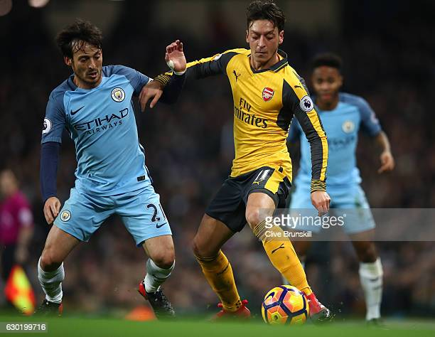 David Silva of Manchester City and Mesut Ozil of Arsenal battle for possession during the Premier League match between Manchester City and Arsenal at...
