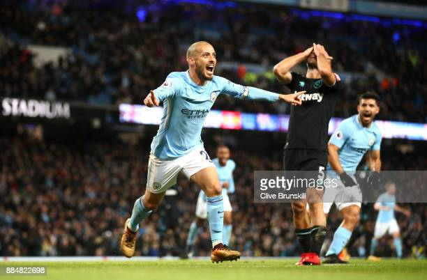David Silva of Manchester City celebrates scoring his sides second goal while Pablo Zabaleta of West Ham United looks dejected during the Premier...