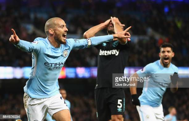 David Silva of Manchester City celebrates scoring his sides second goal with team mate Sergio Aguero while Pablo Zabaleta of West Ham United looks...