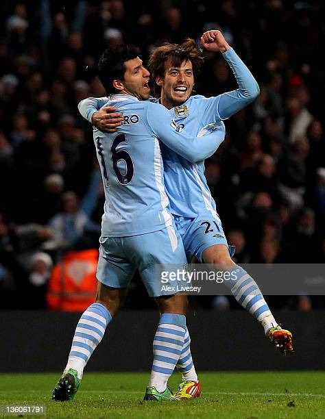 David Silva of Manchester City celebrates scoring the opening goal with team mate Sergio Aguero during the Barclays Premier League match between...
