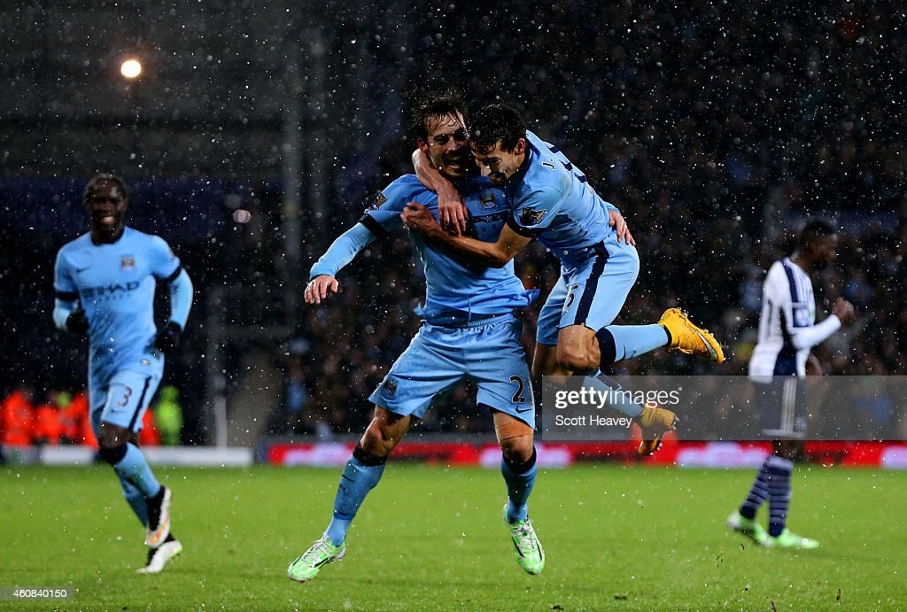 <a gi-track='captionPersonalityLinkClicked' href=/galleries/search?phrase=David+Silva&family=editorial&specificpeople=675795 ng-click='$event.stopPropagation()'>David Silva</a> of Manchester City celebrates with team-mate Jesus Navas after scoring his team's third goal during the Barclays Premier League match between West Bromwich Albion and Manchester City at The Hawthorns on December 26, 2014 in West Bromwich, England.