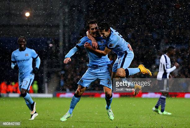 David Silva of Manchester City celebrates with teammate Jesus Navas after scoring his team's third goal during the Barclays Premier League match...