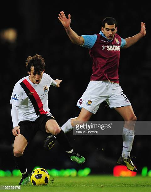 David Silva of Manchester City holds off the challenge of Tal Ben Haim of West Ham United during the Barclays Premier League match between West Ham...