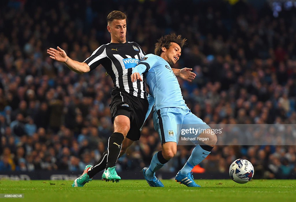 David Silva of Manchester City is tackled by Ryan Taylor of Newcastle United during the Capital One Cup Fourth Round match between Manchester City and Newcastle United at Etihad Stadium on October 29, 2014 in Manchester, England.