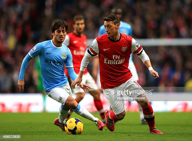 David Silva of Manchester City marshalls Mesut Oezil of Arsenal during the Barclays Premier League match between Manchester City and Arsenal at...