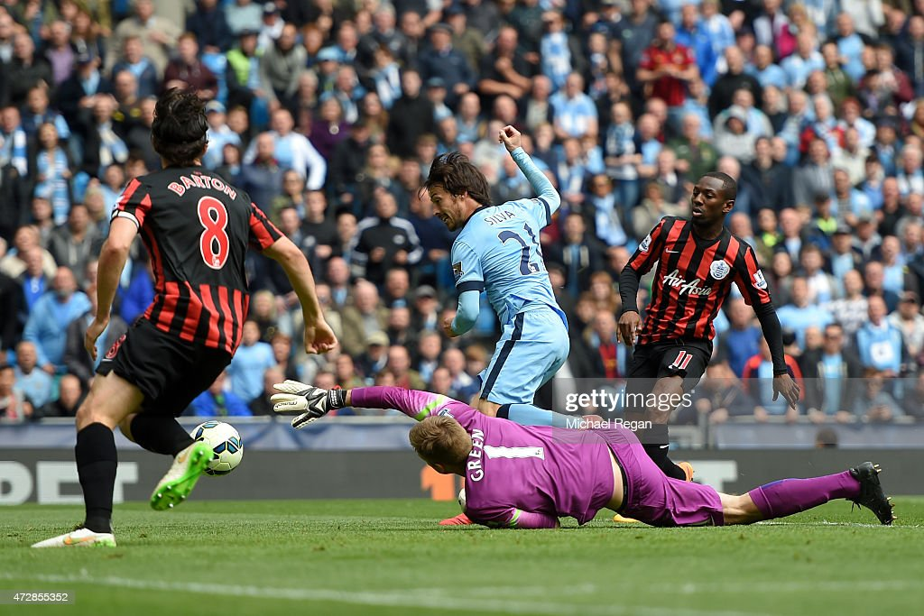 David Silva of Manchester City scres his team's sixth goal past the outstretched Robert Green of QPR during the Barclays Premier League match between Manchester City and Queens Park Rangers at the Etihad Stadium on May 10, 2015 in Manchester, England.