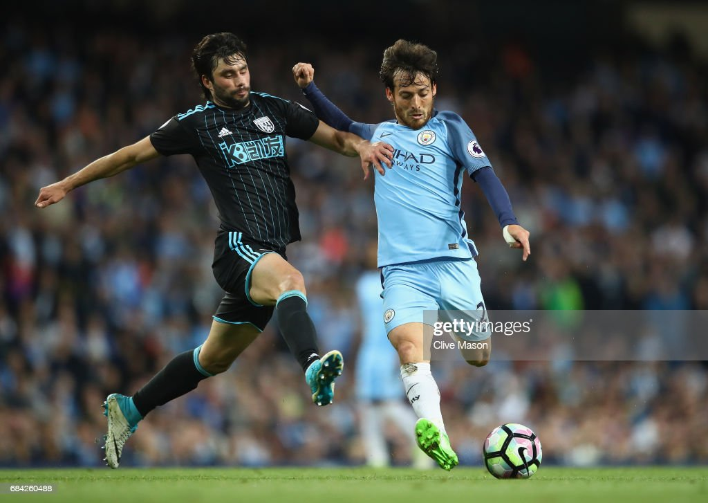 David Silva of Manchester City shoots past Claudio Yacob of West Bromwich Albion during the Premier League match between Manchester City and West Bromwich Albion at Etihad Stadium on May 16, 2017 in Manchester, England.