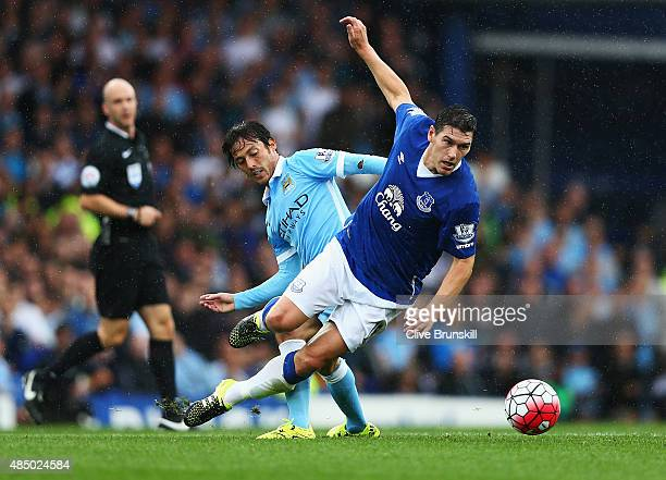 David Silva of Manchester City tackles Gareth Barry of Everton during the Barclays Premier League match between Everton and Manchester City at...