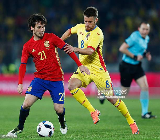 David Silva of Spain battles for the ball with Mihai Pintilii of Romania during the International Friendly match between Romania and Spain held at...