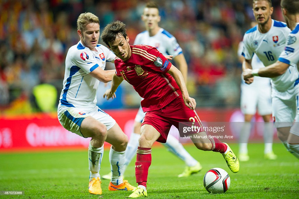 David Silva of Spain duels for the ball with Tomas Hubocan of Slovakia during the Spain v Slovakia EURO 2016 Qualifier at Carlos Tartiere on...
