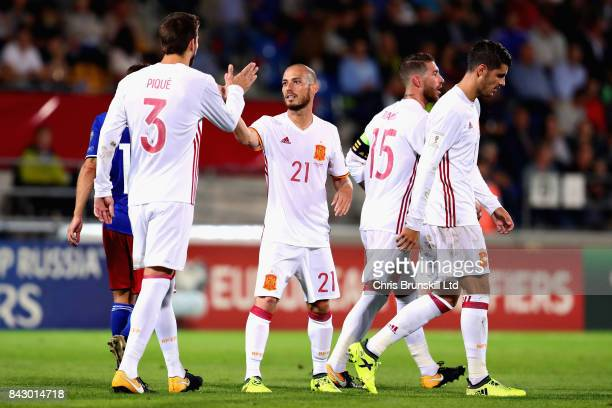 David Silva of Spain is congratulated by teammate Gerard Pique after scoring his sides fourth goal during the FIFA 2018 World Cup Qualifier between...