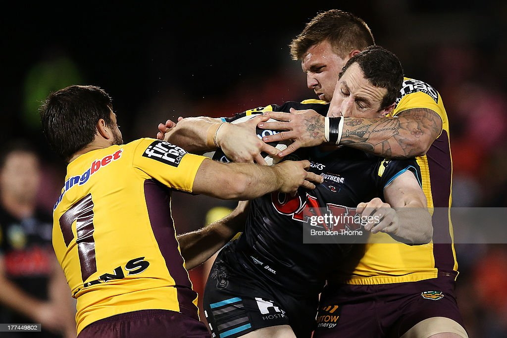 David Simmons of the Panthers is tackled by Ben Hunt and Josh McGuire of the Broncos during the round 24 NRL match between the Penrith Panthers and the Brisbane Broncos at Centrebet Stadium on August 23, 2013 in Sydney, Australia.