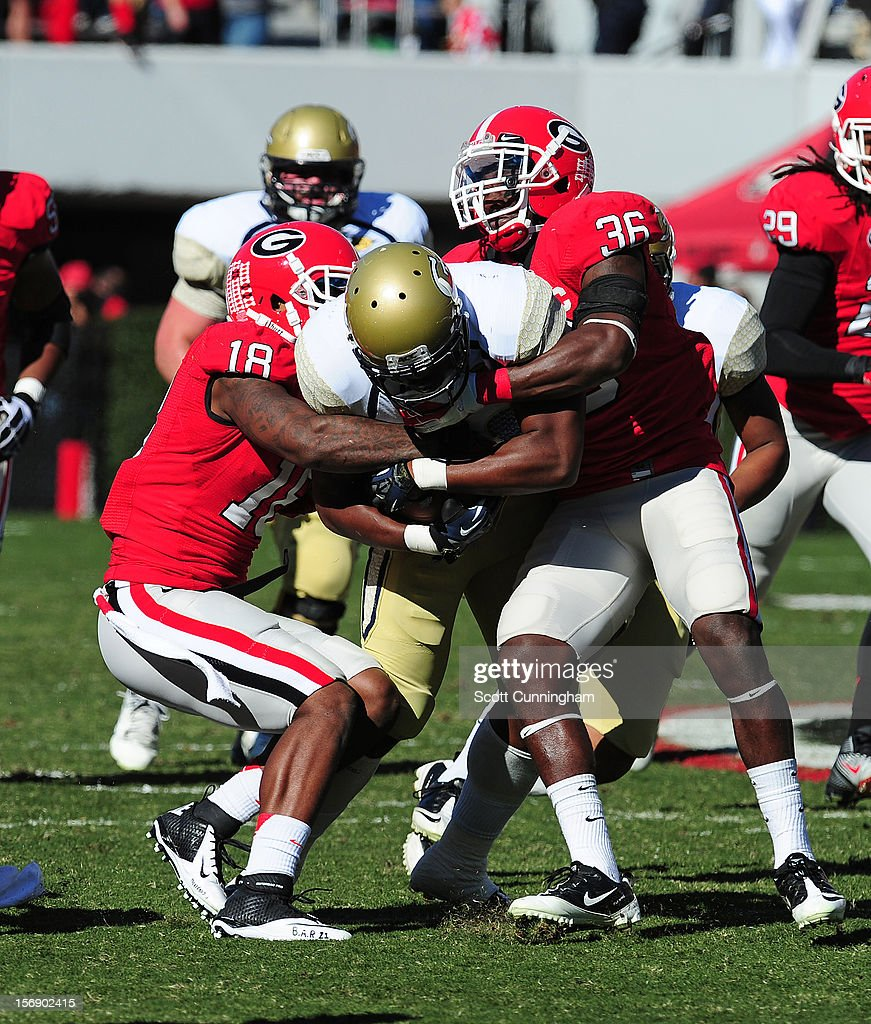 David Sims #20 of the Georgia Tech Yellow Jackets is tackled by Bacarri Rambo #18 and Shawn Williams #36 of the Georgia Bulldogs at Sanford Stadium on November 24, 2012 in Athens, Georgia.