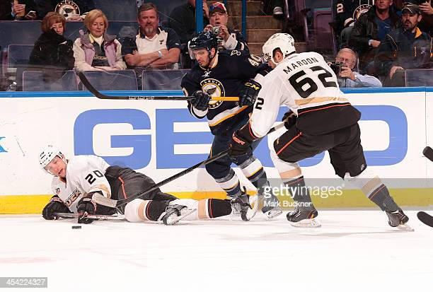 David Steckel and Patrick Maroon of the Anaheim Ducks battle for the puck with Maxim Lapierre of the St Louis Blues during an NHL game on December 7...