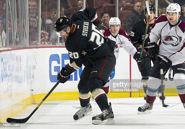 David Steckel of the Anaheim Ducks passes the puck with PA Parenteau and John Mitchell of the Colorado Avalanche in pursuit April 10 2013 at Honda...