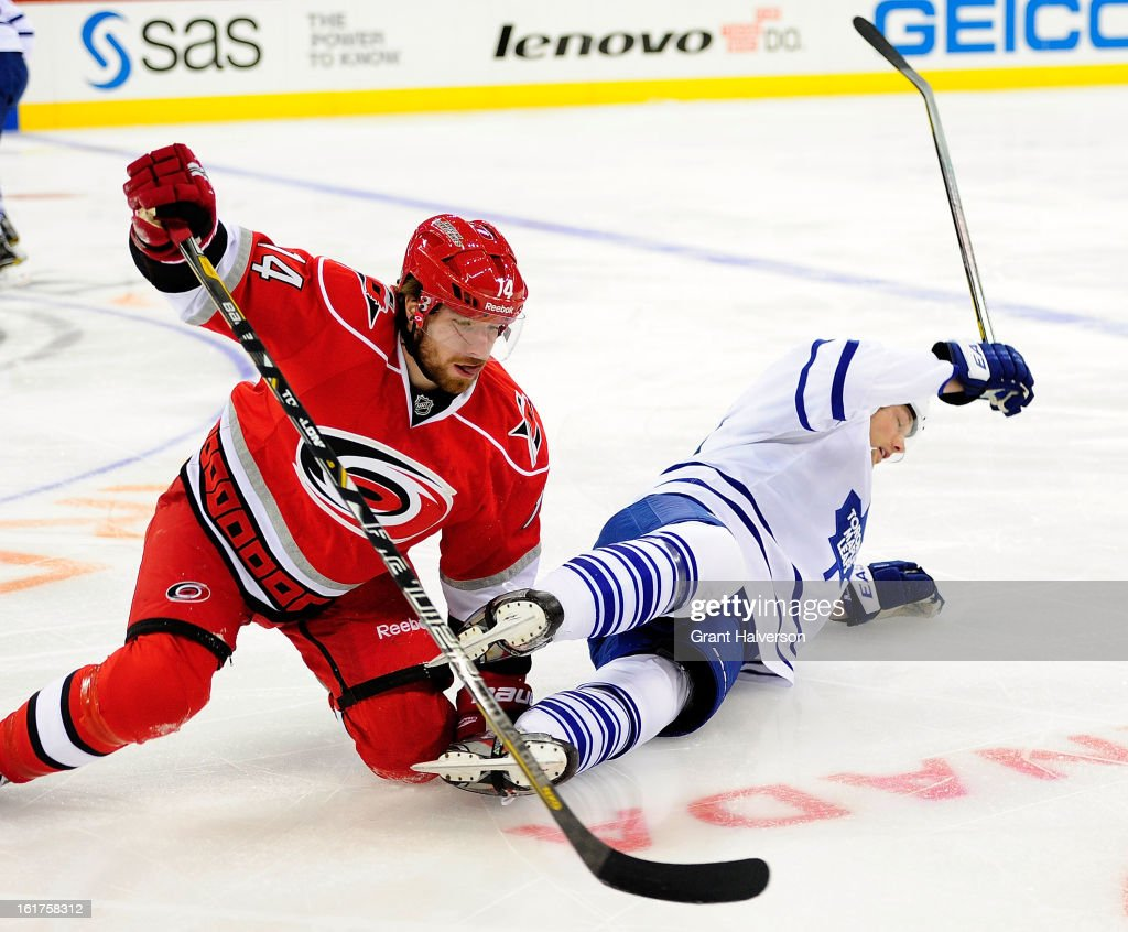 David Steckel #20 of the Toronto Maple Leafs goes to the ice with Andreas Nodl #14 of the Carolina Hurricanes during play at PNC Arena on February 14, 2013 in Raleigh, North Carolina. Carolina defeated Toronto 3-1.