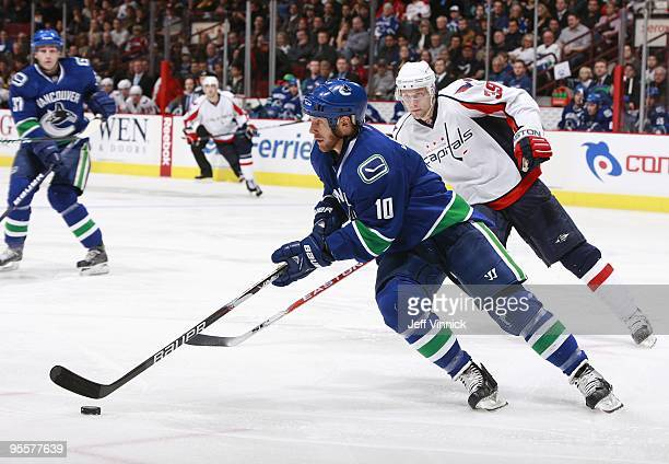 David Steckel of the Washington Capitals looks on as Ryan Johnson of the Vancouver Canucks skates up ice with the puck during their game at General...