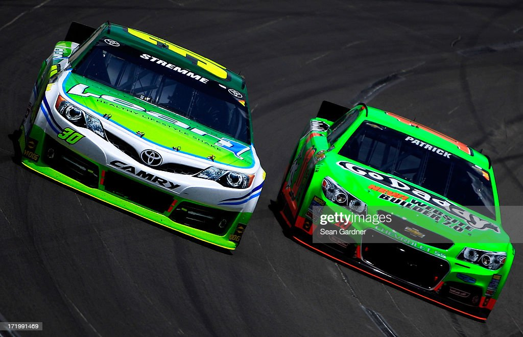 David Stremme, driver of the #30 Lean 1 Toyota, and Danica Patrick, driver of the #10 GoDaddy.com Chevrolet, race during the NASCAR Sprint Cup Series Quaker State 400 at Kentucky Speedway on June 30, 2013 in Sparta, Kentucky.