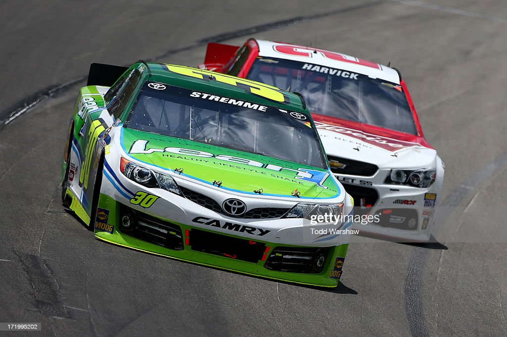 David Stremme, driver of the #30 Lean 1 Toyota, races Kevin Harvick, driver of the #29 Budweiser Chevrolet, during the NASCAR Sprint Cup Series Quaker State 400 at Kentucky Speedway on June 30, 2013 in Sparta, Kentucky.