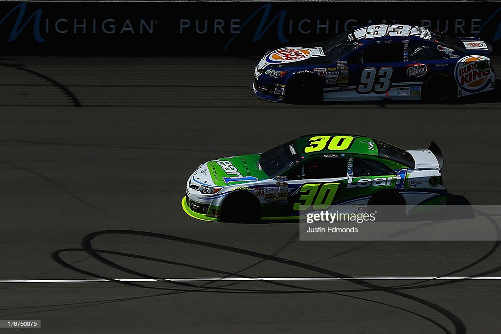 David Stremme, driver of the #30 Lean1 Toyota, races Travis Kvapil, driver of the #93 Burger King / Dr. Pepper Toyota, during the NASCAR Sprint Cup Series 44th Annual Pure Michigan 400 at Michigan International Speedway on August 18, 2013 in Brooklyn, Michigan.