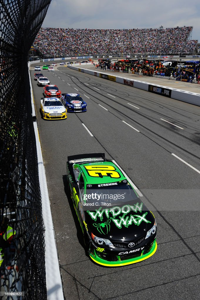 David Stremme, driver of the #30 Widow Wax Toyota, leads a group of cars down the frontstretch during the NASCAR Sprint Cup Series STP Gas Booster 500 on April 7, 2013 at Martinsville Speedway in Ridgeway, Virginia.