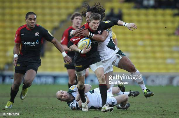David Strettle of Saracens is tackled by Seilala Mapasua and Paul Hodgson during the Aviva Premiership match between Saracens and London Irish at...