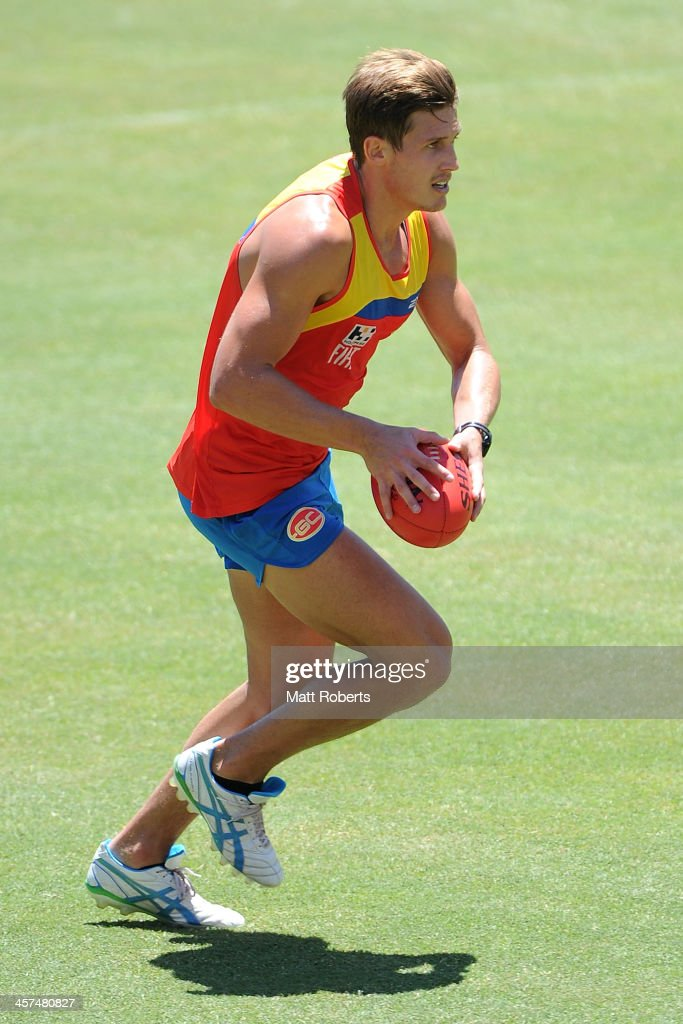 David Swallow runs with the ball during a Gold Coast Suns AFL pre-season training session at Metricon Stadium on December 18, 2013 on the Gold Coast, Australia.