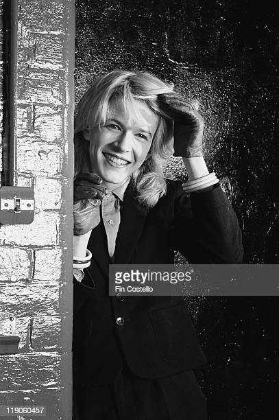 David Sylvian singer with British New Wave band Japan smiling as he poses for a studio portrait beside a painted brick wall in February 1979