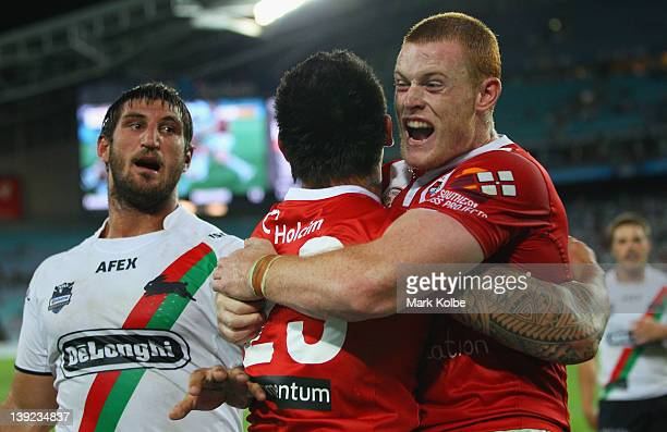 David Taylor of the Rabbitohs looks on as Daniel Vidot of the Dragons is congratulated by Nathan Green of the Dragons after he scored a try during...