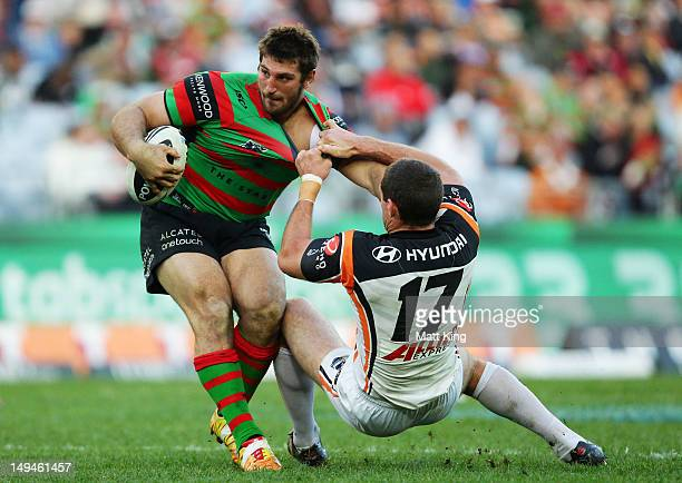David Taylor of the Rabbitohs puts a fend on Ray Cashmere of the Tigers during the round 21 NRL match between the South Sydney Rabbitohs and the...