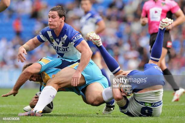 David Taylor of the Titans is tackled by Josh Jackson and Josh Reynolds of the Bulldogs during the round 26 NRL match between the Gold Coast Titans...