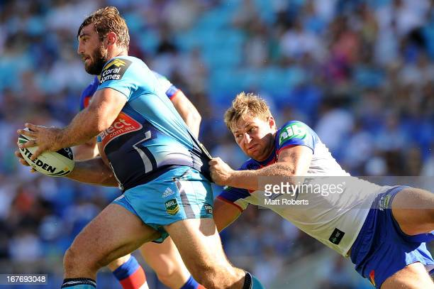 David Taylor of the Titans is tackled during the round seven NRL match between the Gold Coast Titans and the Newcastle Knights at Skilled Park on...