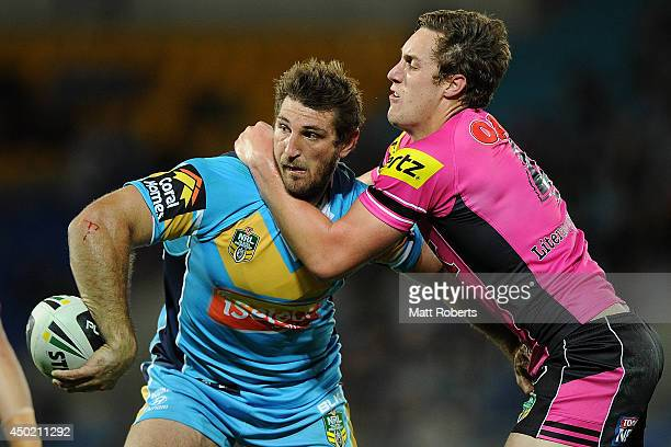 David Taylor of the Titans passes the ball in the tackle during the round 13 NRL match between the Gold Coast Titans and the Penrith Panthers at Cbus...