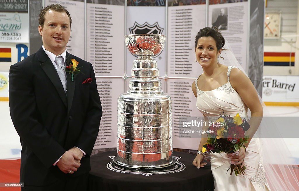 David Thebault and his bride Beth Crosier pose for a picture with the Stanley Cup on their wedding day at the Stirling and District Recreation Centre during Kraft Hockeyville Day 2 on September 14, 2013 in Stirling, Ontario, Canada.