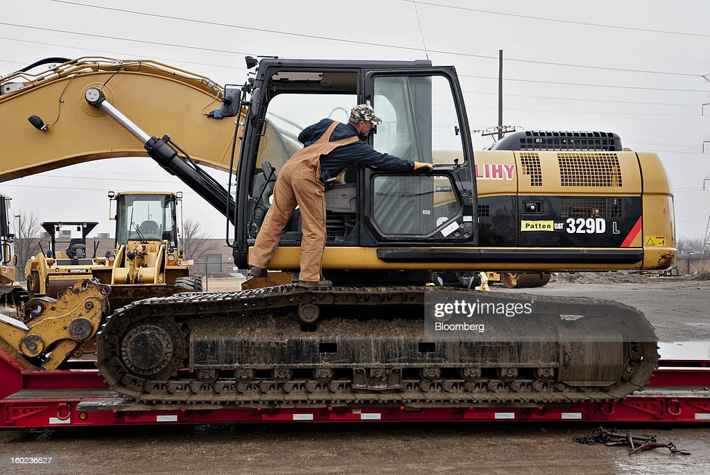 David Thompson, a driver for Herlihy Mid-Continent Construction, loads a Caterpillar Inc. 329D excavator after routine maintenance was performed at a Patten Industries Inc. dealership in Elmhurst, Illinois, U.S., on Monday, Jan. 28, 2013. Caterpillar Inc., the largest maker of construction and mining equipment, said gains in its sales and profit this year will come in the second half as the world economy improves. Photographer: Daniel Acker/Bloomberg via Getty Images