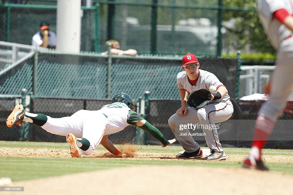 David Thompson #19 of the Miami Hurricanes gets back to first base safely ahead of the throw to Frank Schwindel #5 of the St John's Red Storm on May 5, 2013 at Alex Rodriguez Park at Mark Light Field in Coral Gables, Florida. Miami defeated St John's 6-4 and swept the weekend series.