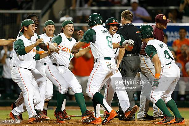 David Thompson of the Miami Hurricanes is congratulated by teammates after scoring the winning run on a wild pitch by Scott Garner of the...