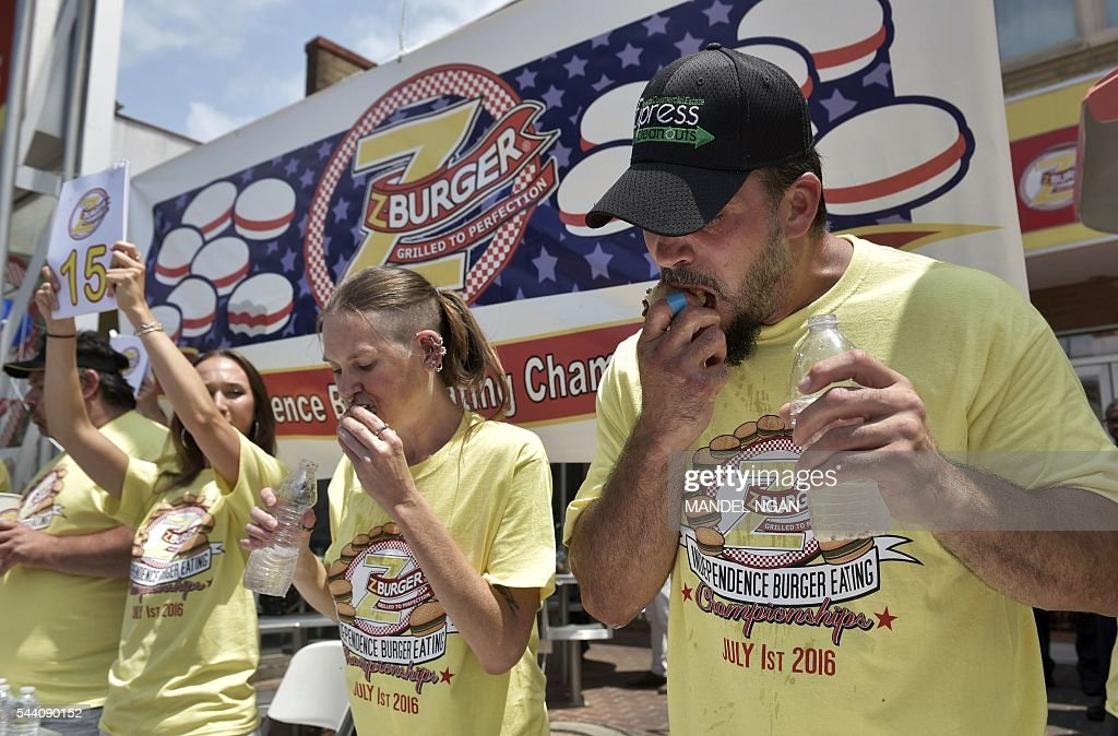 David 'Tiger Wings and Things' Brunelli (R) and Molly Schuyler, who won by eating 28 burgers in 12 minutes, compete in the Zburger Independence Burger Eating Championship on July 1, 2016 in Washington, DC. / AFP / Mandel Ngan