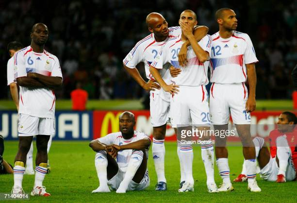 David Trezeguet of France is consoled by his team mates following his team's defeat in a penalty shootout at the end of the FIFA World Cup Germany...