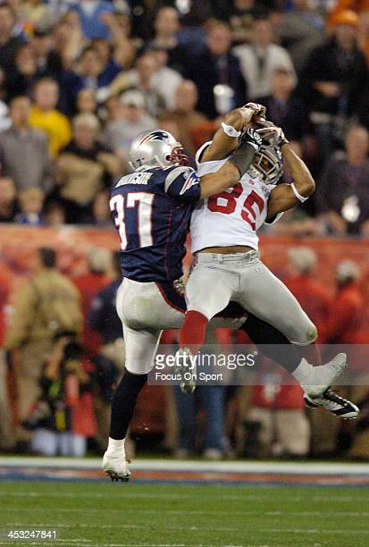 David Tyree of the New York Giants catches this pass over Rodney Harrison of the New England Patriots during Super Bowl XLII on February 3 2008 at...