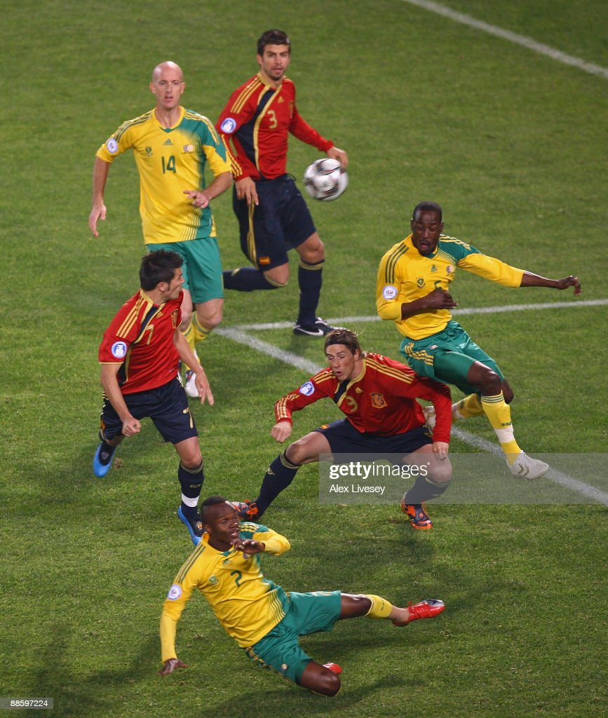 David Villa and Fernando Torres of Spain challenge Siboniso Gaxa and Benson Mhlongo of South Africa for a high ball as Matthew Booth of South Africa...