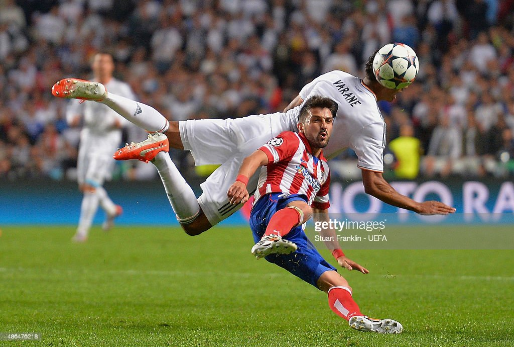 David Villa of Club Atletico de Madrid challenges for the ball with Raphael Varane of Real Madrid during the UEFA Champions League Final between Real Madrid CF and Club Atletico de Madrid at Estadio da Luz on May 24, 2014 in Lisbon, Portugal.
