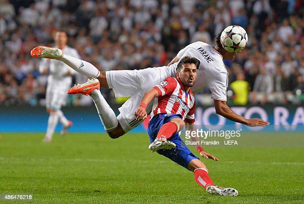 LISBON PORTUGAL MAY 24 David Villa of Club Atletico de Madrid challenges for the ball with Raphael Varane of Real Madrid during the UEFA Champions...