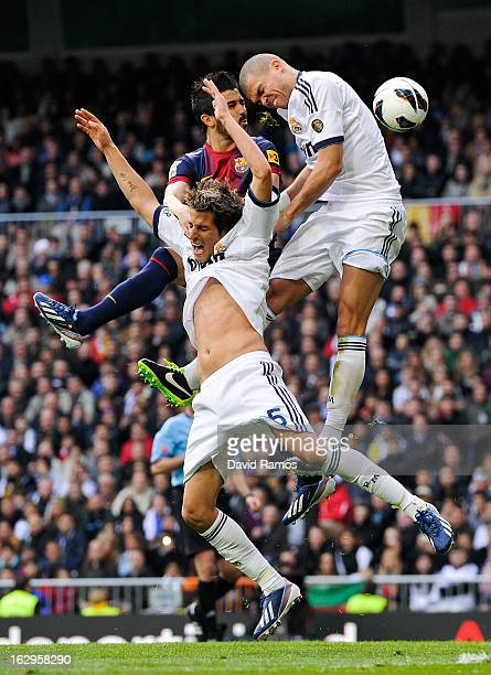 David Villa of FC Barcelona duels for a high ball with Fabio Coentrao and Pepe of Real Madrid CF during the La Liga match between Real Madrid CF and...